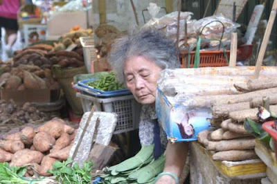 Image of an old granny resting in her market stall