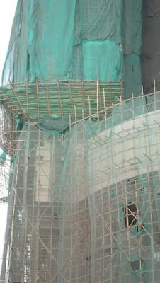 Image of a more substantial bamboo scaffolding on a building site, with green mesh to prevent tools or material from falling out while allowing the wind to pass through with relative ease.