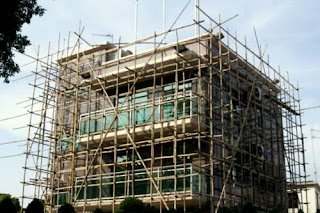 Image of a small house in Hong Kong surrounded with bamboo scaffolding for the workers to walk on.