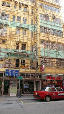 Image of a small building undergoing renovations with bamboo scaffolding around it in Hong Kong.