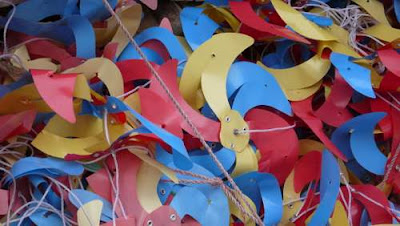 Image of a pile of brightly coloured, festive plastic wind whirlers lying on the ground.