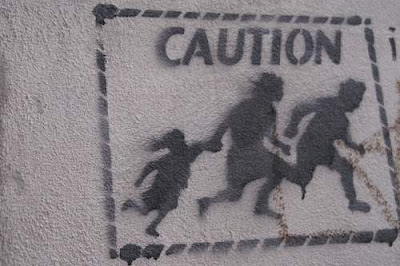 Graffiti image of a family fleeing, sprayed on a wall, from the old town centre of Genoa, Italy.