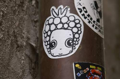Graffiti image of a sticker of a berry princess hipsterette from the Old Town centre of Genoa, Italy.