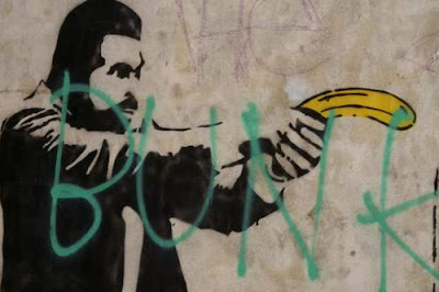 Graffiti image of Hutch, from the old USA TV show 'Starsky and Hutch'... with an absurdist banana drawn instead of guns, from the old town centre of Genoa, Italy.
