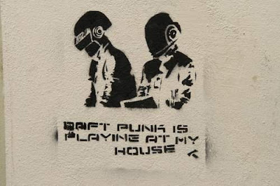 Graffiti image of two men in space helmets and the message 'Daft Punk is playing at my house' from the old town centre of Genoa, Italy.