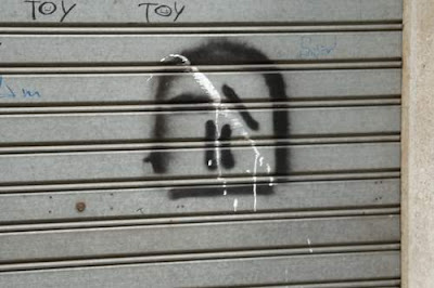 Graffiti image of a very minimal man skull, vaguely resembling a neanderthal skull, from the old town centre of Genoa, Italy.