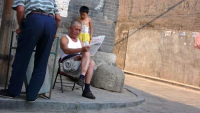 Image of a man sitting outside, reading the paper, with a child peering down and over his shoulder, from a perch on a rock, taken in Pingyao, Shanxi Province, China.
