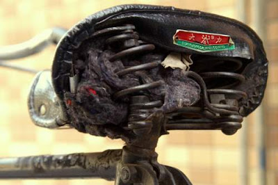 Image of a bicycle seat losing its stuffing, in China, seat manufactured by Suong Zong Dalian Zuo Chang.