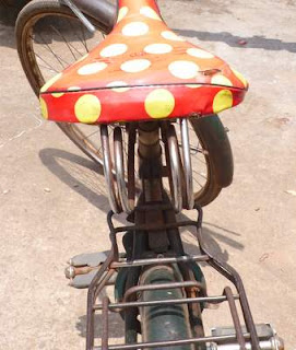 Image of a great, red with huge yellow polka-dotted bicycle saddle found in Bhubaneshwar, Orissa (India).