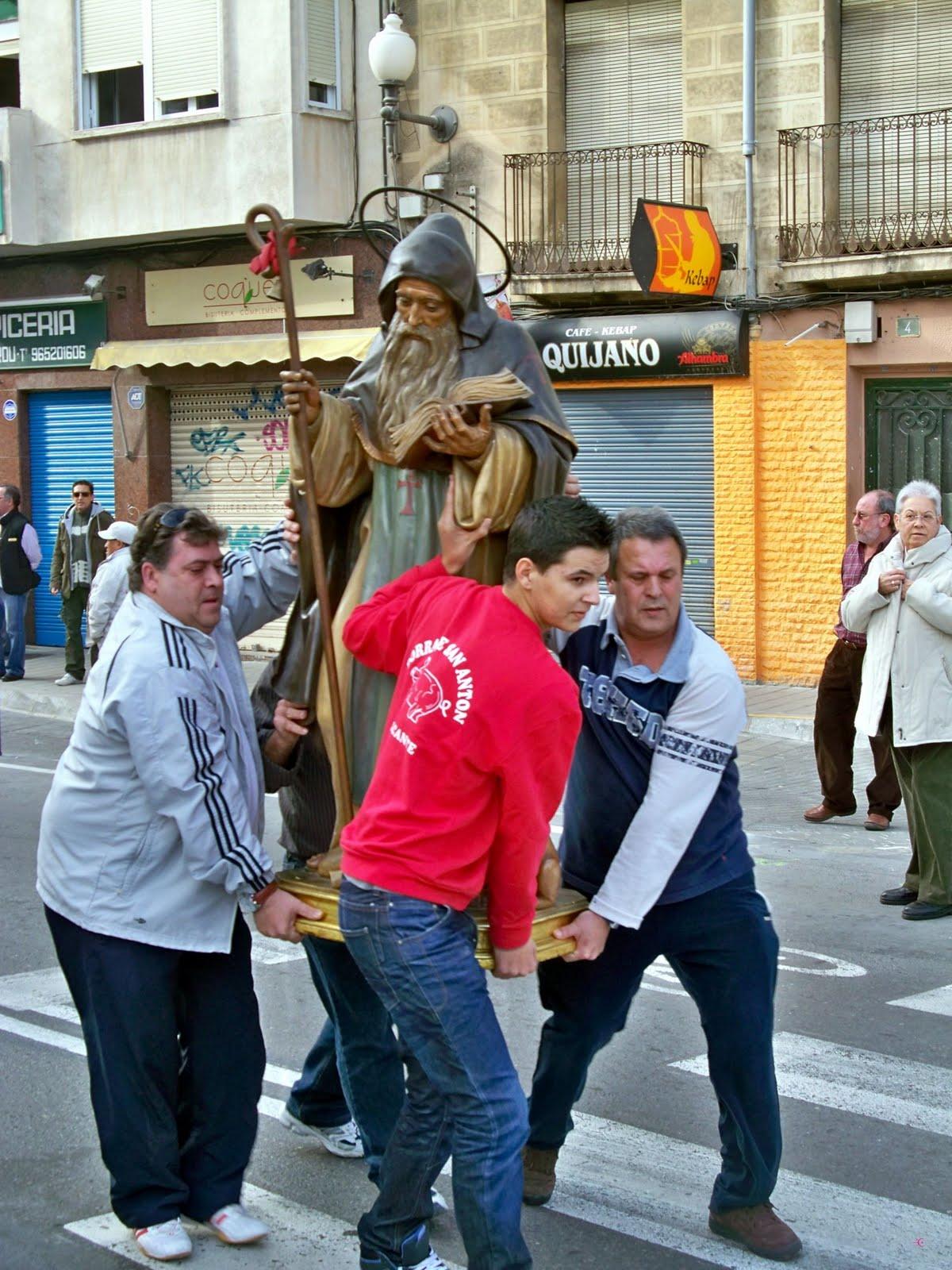 Miembros de la comisión de fiestas de San Antón y vecinos portando la figura de dicho santo.