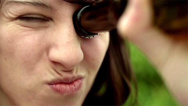 Chica intentando abrir una cerveza con el ojo en el Anuncio San Miguel Abrefácil Te lo merecías. Destapa una San Miguel como nunca antes - Donde va, triunfa Febrero 2011