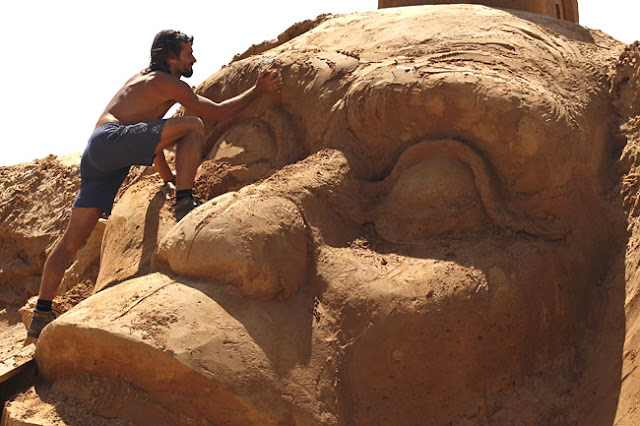 a man works on a sand sculpture of a primate