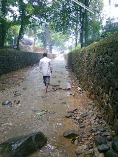 man going alone on a wet way was my picture taken on my Nokia Mobile from Kottiyoor temple Kannur District Kerala where believes to be the Dakshayagam performed by the father-in-law of Lord Shiva which won prize from Malayala Manorama Mazha Mobile Photography Contest – fantastic shot