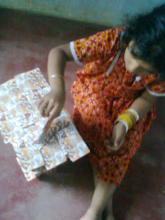 cute Indian baby with pink and red dress sitting a corner and trying to build palace with playing cards