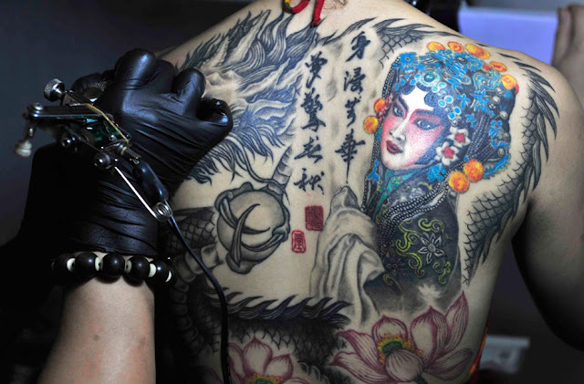 An artist works on a customer at the National Tattoo Competition in Shenyang
