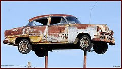 old rusted car on pole