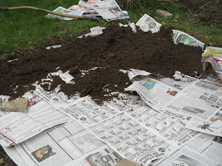 Filling garden in with topsoil after laying down newspaper