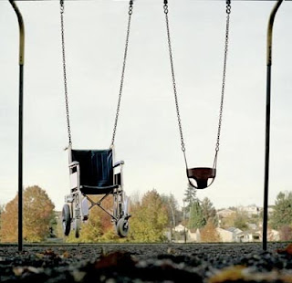 really odd photo of wheelchair in kids swings