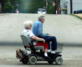funny jokes photos two old people in a small motorised scooter sitting on lap