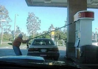 funny photo of gas station guy stretching the hose to cars tank