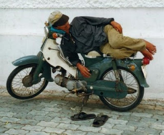 funny photo of man sleeping on his motorbike crazy