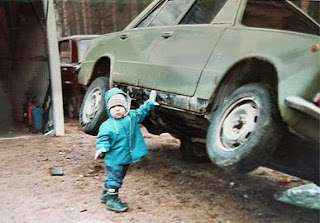 funny superboy photo lifting green car with one hand