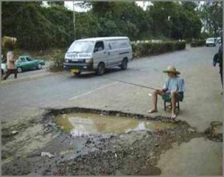 funny fishing photos man in road trying to catch fish in pot hole or puddle
