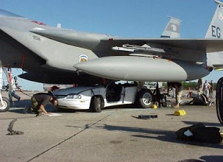 weird photo of car crushed underneath an air force fighter jet accident or movie set