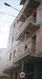 really crazy building photo of lamp post built around balconys funny