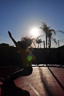 Sara em pleno salto no pula pula, com braços e cabelos pro ar, e o sol de fundo