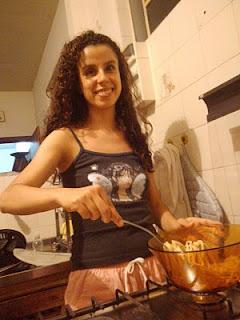 Sara, sorrindo feliz, mexendo o mesmo macarrão no fogão.