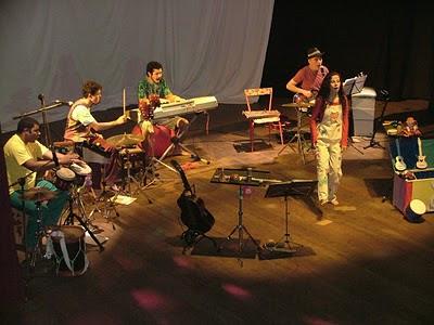 """Os músicos Adelmo Machado e Fred Portilho (percussão), Bianco Marques (teclado e voz), Sérgio Bentes (contrabaixo e voz) e Sara Bentes (cantando, de pé no centro do palco), em apresentação do show """"Onde é que foi parar?"""""""