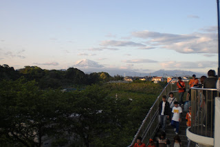 Fans file out as Mount Fuji looms in the background