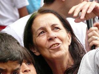 Foto mostra um close de rosto da tia Dag, ela tem os cabelos negros, lisos, na altura do ombro. Dagmar Garroux olha para o horizonte e está acompanhada de dois meninos, que só podemos ver um pedaço de suas cabeças, pois a foto está cortada.