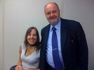 Foto de Mara Gabrilli, à esquerda, de blusa cinza de mangas curtas e um estampado sorriso no rosto ao ser clicada ao lado do Desembargador Malheiros, um senhor alto, de terno escuro, camisa e gravatas azuis, que a abraça carinhosamente. Ambos olham para a frente.