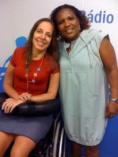 Mara Gabrilli, de blusa, saia e colar de flores, ao lado de Clarice Oliveira, com vestido cinza, cabelos cacheados soltos no ombro