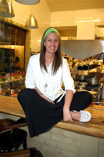Morena Leite sentada na cozinha em que trabalha