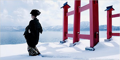 A Japanese woman in traditional dress outside a demonic shrine walking in the snow.
