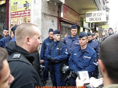 egy betépett rendőr Tomcatet bűvőli, háttérben a zseniális vírusreklámmal befuttatott jegyiroda: Budapest összes szkinhede és zsidaja kötelességének érzi, hogy itt vásároljon