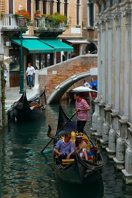 A Gondola navigating a canal - Venice, Italy