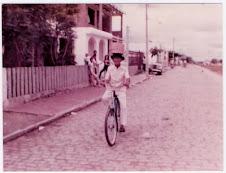 Aurino de bike com um cesto na cabeça.
