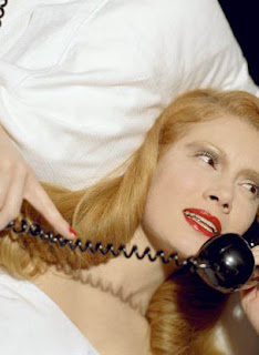woman in bed talking on the phone