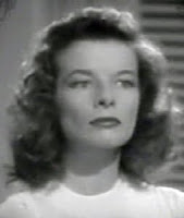 Head and shoulders of Katharine Hepburn, from The Philadelphia Story, looking severe and serious.
