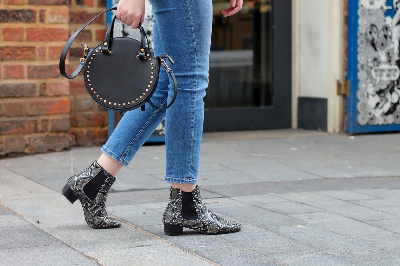 topshop circle round cross body bag with studs in black, blue jeans and asos snake print ankle boots
