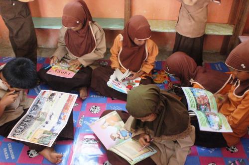 Anak-anak semangat membaca buku yang kami bawa untuk perpus sekolah mereka