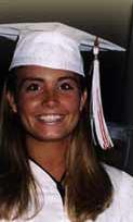A smiling young white woman with long, straight blond hair, dressed in white graducation cap and gown