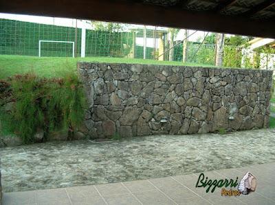 Muro de pedra construído com pedra moledo para formar o platô para a construção do campo de futebol com grama esmeralda.
