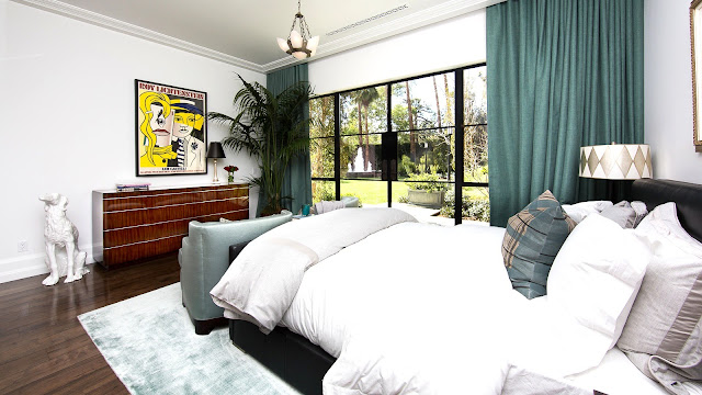 Guest bedroom mansion wood floor turquoise curtains picture window wood drawers black leather bed