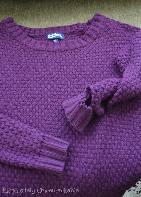 Purple sweater with torn sleeve cuff