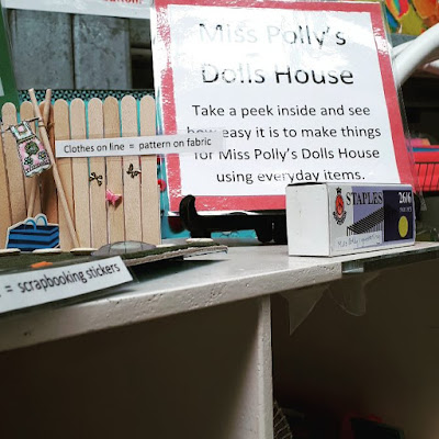 A variety of dolls' house decorating ideas displayed with signs explaining what they are made of. Next to them is a larger sign that says 'Miss Polly's Dolls House. Take a peek inside and see how easy it is to make things for Miss Polly's Dolls House using everyday items.